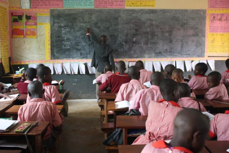 Teacher in clasroom at REACH for Uganda